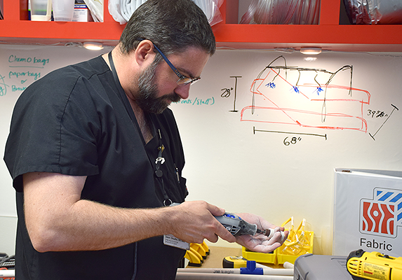 Nurse Jason Schaeffer works on constructing a hand-held shower device for the hospital's burn victims.