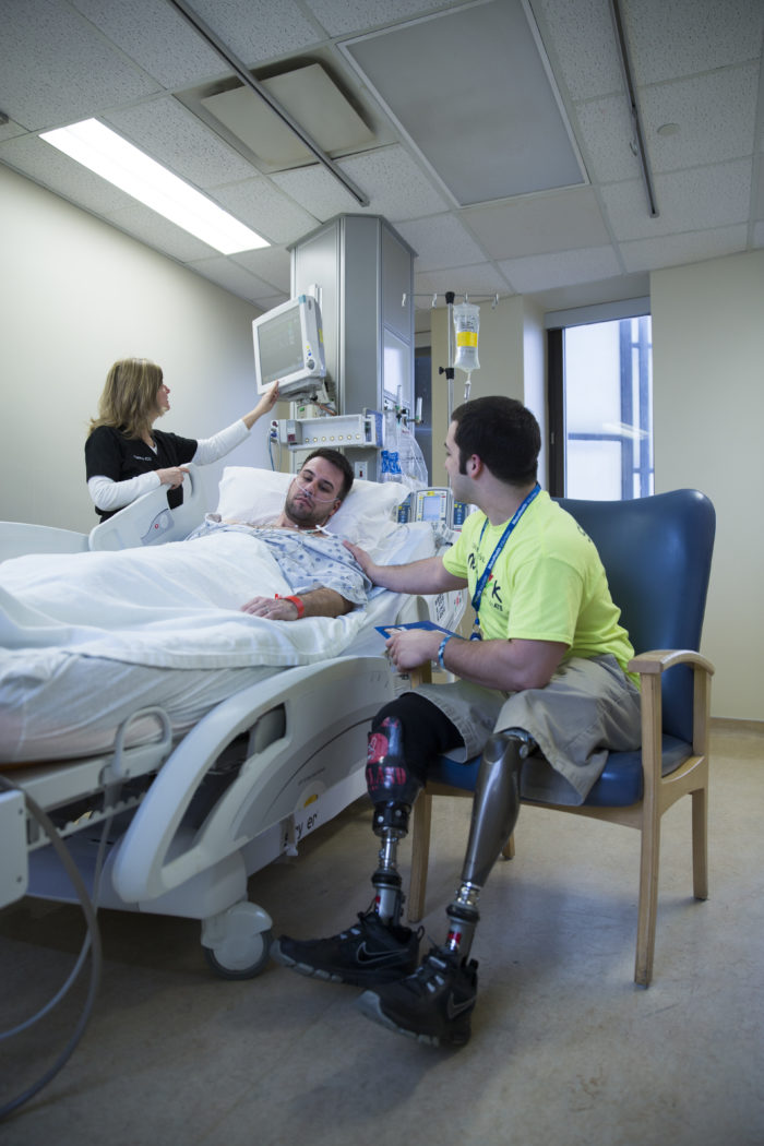 A man with prosthetic legs sits by a man in a hospital bed.